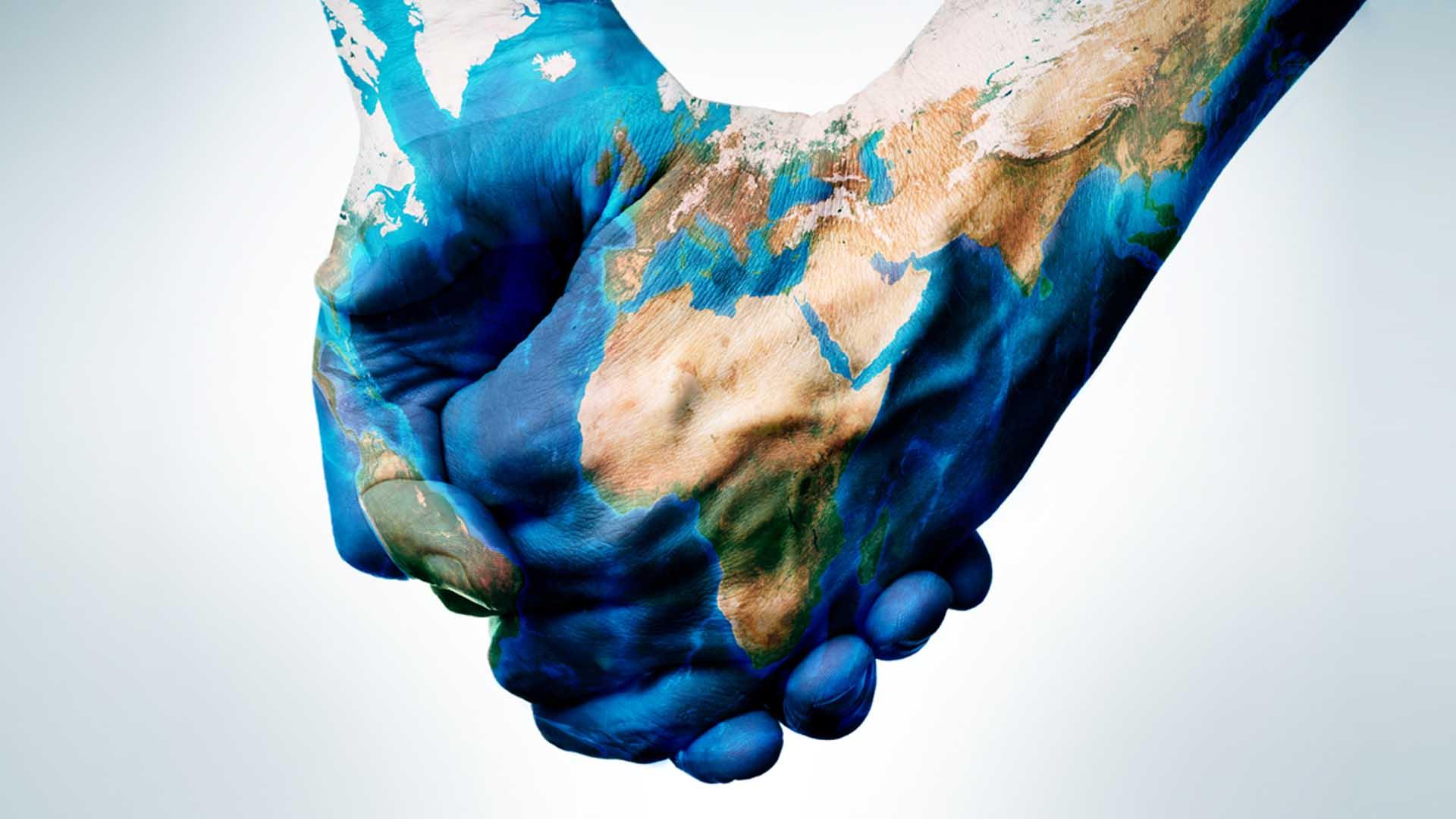 Mani con sopra proiettato il mondo che si uniscono